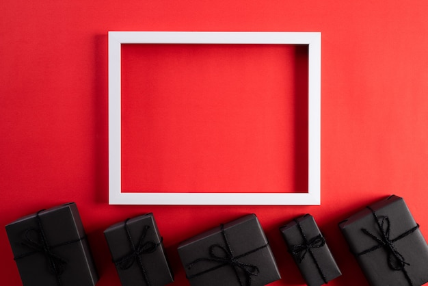 White picture frame with black gift box on red background. black friday concept