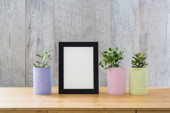 White picture frame with cactus plants in painted can on wooden desk