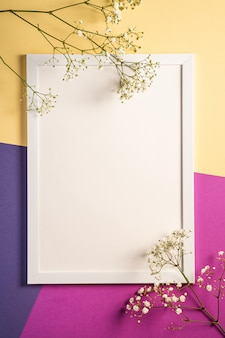White picture frame with empty template, gypsophila flowers, cream, blue and purple colored background, mockup card