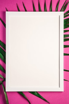 White picture frame with empty template on palm leaves, pink purple background