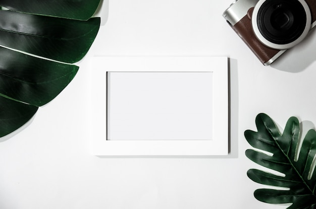 White picture frame with green leaves and camera on white isolated