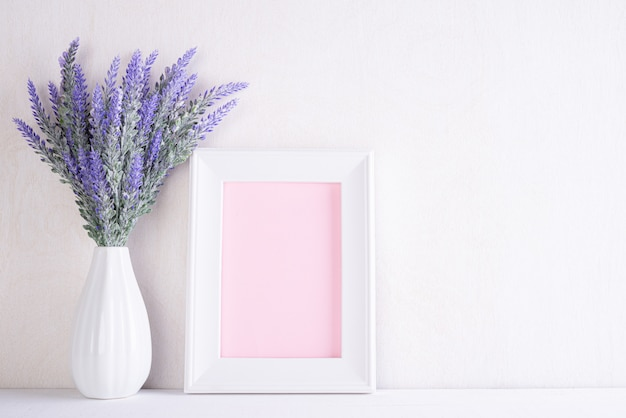 White picture frame with lovely purple flower in vase on white wooden table