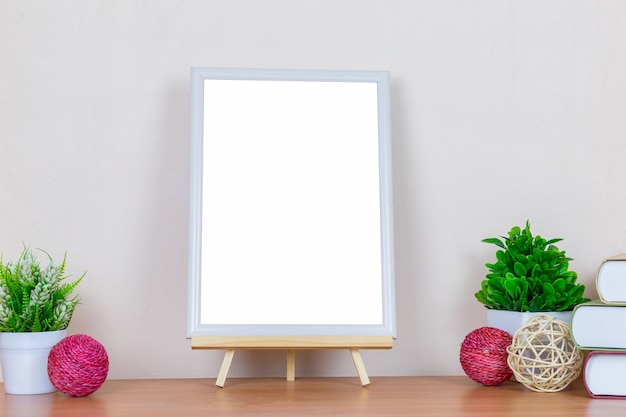 White picture frame on wood table.