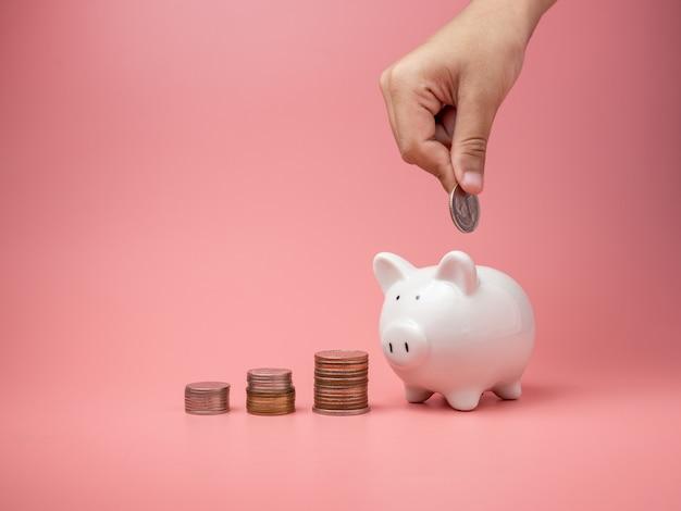 白い貯金箱と人間の手で貯金箱にコインを入れるコイン