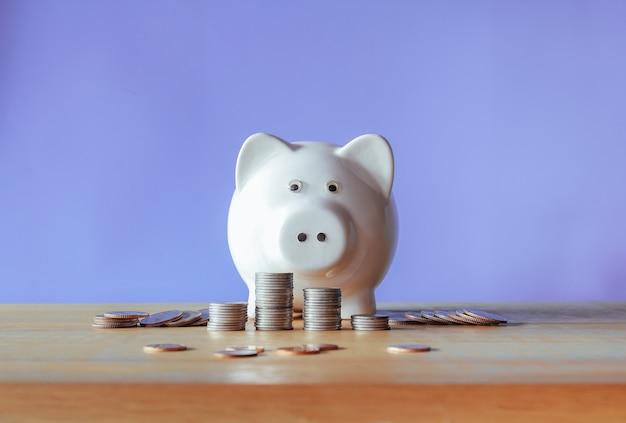 흰색 돼지 저금통과 보라색 배경 저축 개념이 있는 나무 책상에 돈 동전 더미