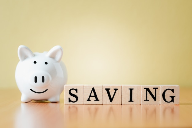 흰색 돼지 저금통 및 태그 단어 저장, 은퇴 기금 및 미래 계획 개념에 대한 돈을 절약하는 성장까지 단계를 계획하는 나무 상자.