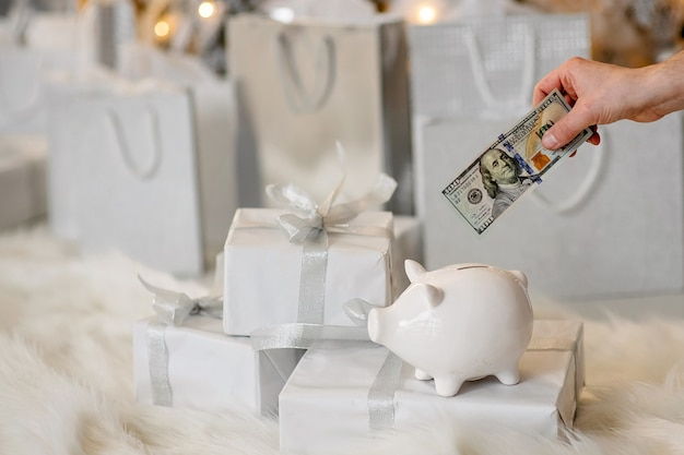 White piggy bank on boxes with gifts and hand holds 100 dollars