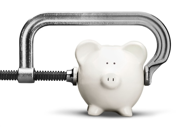 White piggy bank and clamp on background