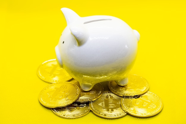White piggy bank lay on the many gold bitcoin over the black background. for saving money wealth and finance concept and the copyspace for design.