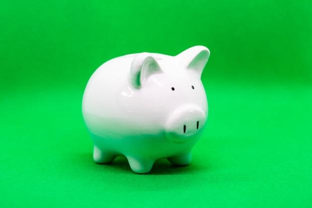 녹색 배경에 있는 흰색 돼지 저금통은 돈과 금융 개념, 디자인을 위한 카피스페이스를 절약할 수 있습니다.