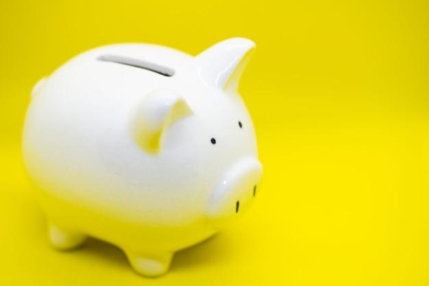 노란색 배경에 있는 흰색 돼지 저금통은 돈과 금융 개념, 그리고 디자인을 위한 카피스페이스를 절약할 수 있습니다.