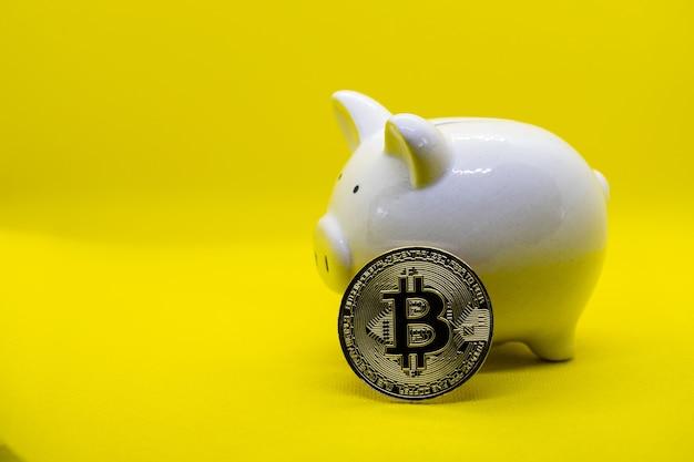노란색 배경에 흰색 돼지 저금통입니다. 돈의 부와 금융 개념과 디자인을 위한 카피스페이스를 절약하기 위한 돼지 저금통.