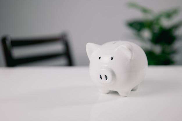 흰색 테이블에 흰색 돼지 저금통입니다. 개념 돈과 금융입니다. 복사 공간