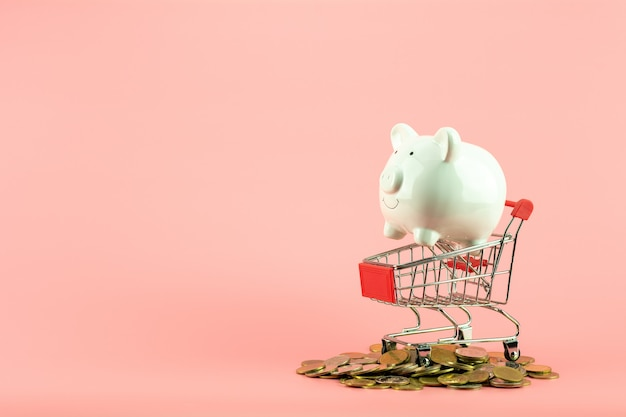 White piggy bank in small shopping cart on pile of golden coins.