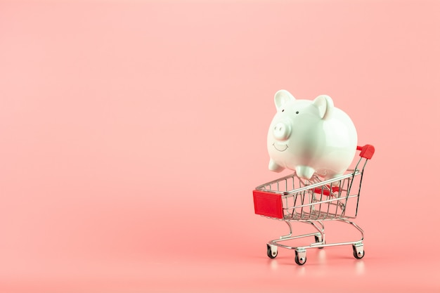 White piggy bank in small shopping cart on pink background. - save and management concept.