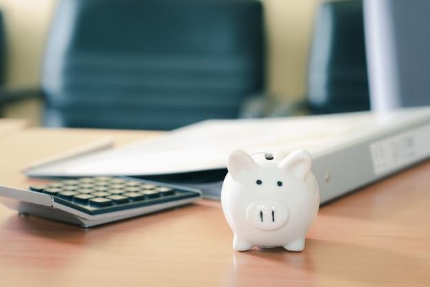 돈으로 저축하고 계획 단계까지 나무 테이블에 계산기가있는 흰색 돼지 저금통, 퇴직 기금 및 미래 계획 개념에 대한 비용 절감.