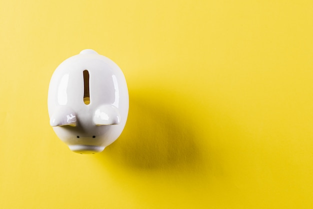 White piggy bank on yellow wall for saving money concept.