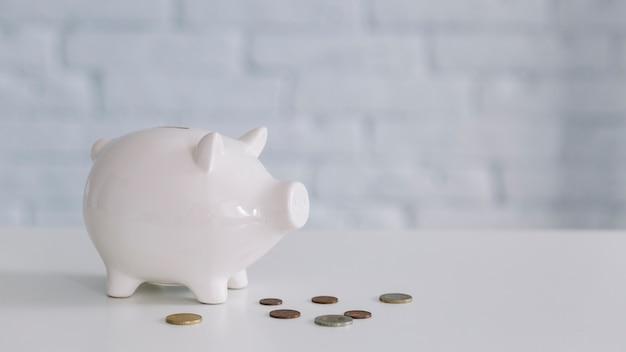 White piggybank and coins on desk