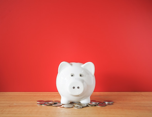 White piggybank and money coin on wooden desk
