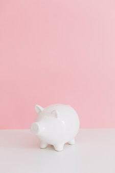 White piggybank on white desk over the pink background