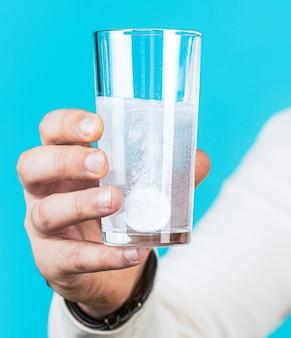 Белая таблетка и стакан воды в руках человека. концепция здоровья.