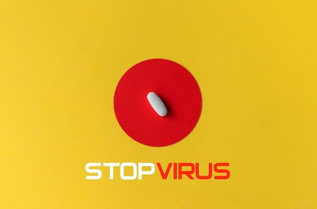 노란색 배경에 비문 중지 바이러스와 빨간색 동그라미에 흰색 알 약. 코로나 바이러스 치료 개념.