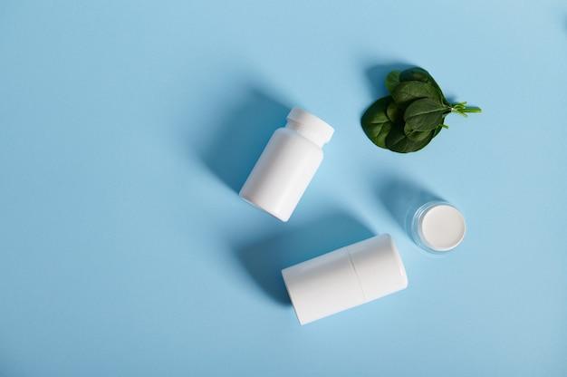 Белые контейнеры для таблеток и молодые листья шпината. плоская композиция