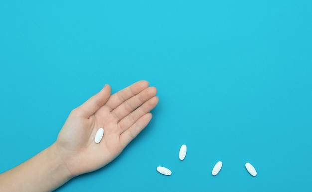 White pill on hand and some pills on blue background. medicine concept.