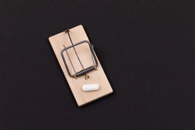 木製のネズミ捕りの製薬中毒の白い錠剤