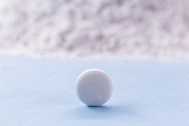 Белая таблетка с оксидом цинка на заднем плане, концепция витамина.