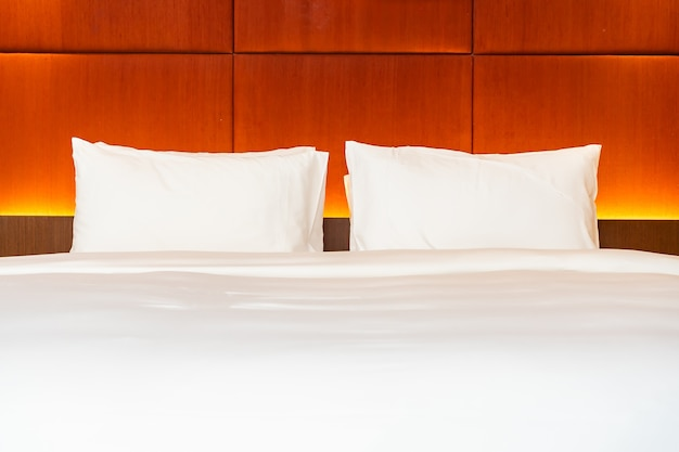 白い枕とベッドルームのライトランプ装飾インテリアとベッドの上の毛布