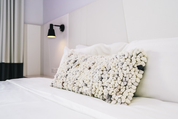 White pillow on bed decoration in beautiful luxury bedroom interior