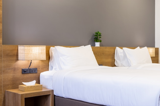 White pillow on bed decoration with light lamp and tissue box in hotel bedroom interior