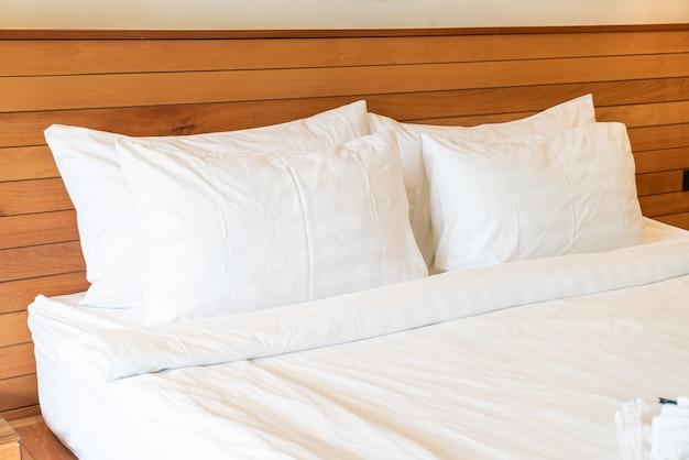 Украшение белой подушки на кровати в интерьере спальни