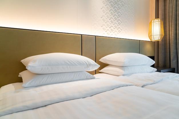 Украшение белой подушкой на кровати в спальне курортного отеля