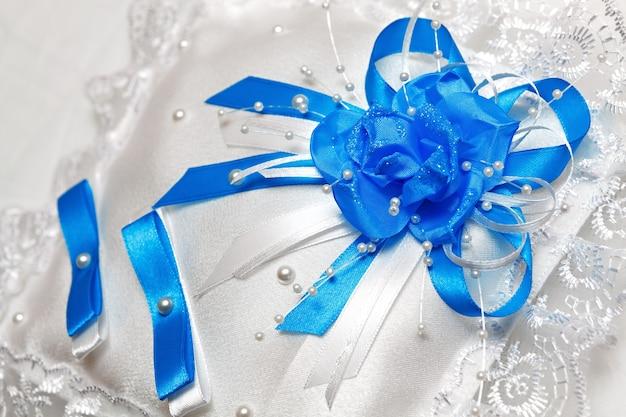 Белая подушка для обручальных колец с синими лентами