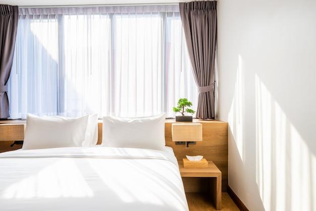 Белая подушка на украшении кровати со светлой лампой и зеленым деревом в вазонах в интерьере спальни отеля