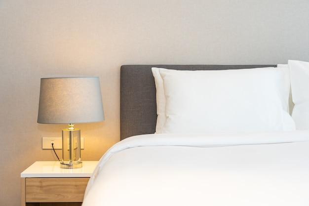Белая подушка на кровати с лампой
