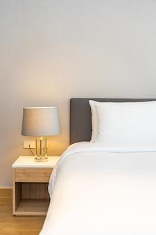 조명 램프와 함께 침대에 흰색 베개