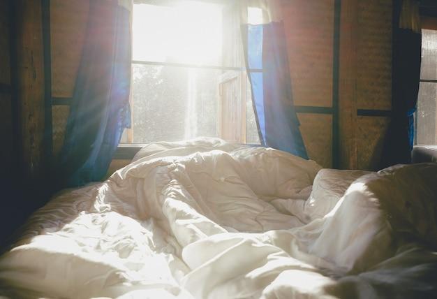 朝の景色の背景ときれいなホテルの寝室の白い枕と寝具シーツ
