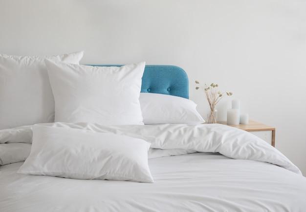 Белые подушки и пуховое одеяло на синей кровати.
