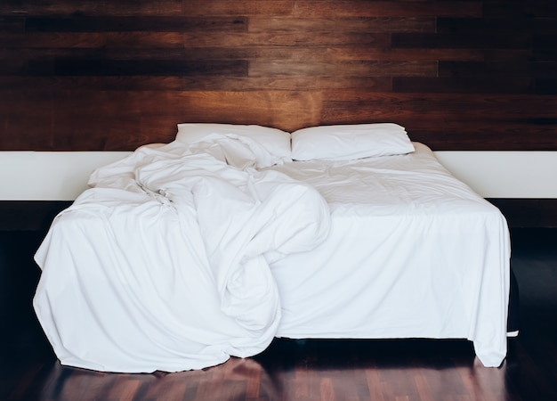 White pillows on bed sheet and blanket with wrinkle messy in the bedroom