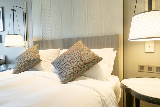 White pillows decoration on bed in bedroom interior