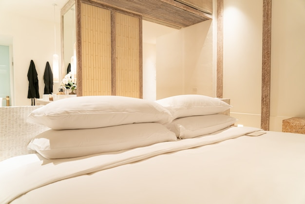 White pillows decoration on bed in luxury hotel resort bedroom