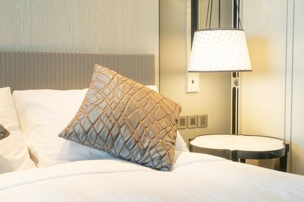 Украшение белых подушек на кровати в спальне