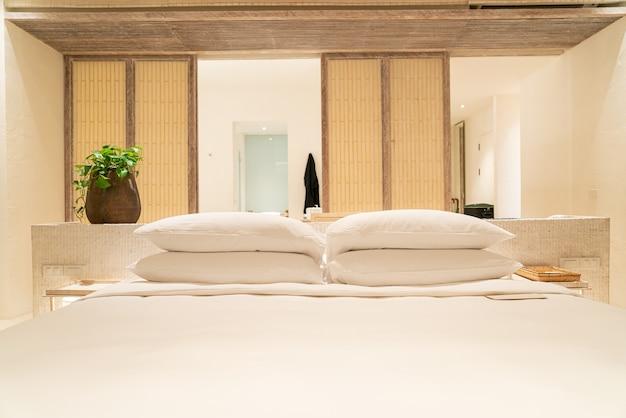 Украшение белыми подушками на кровати в роскошной спальне курортного отеля