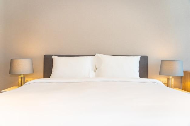 Белые подушки на кровати с легкими лампами