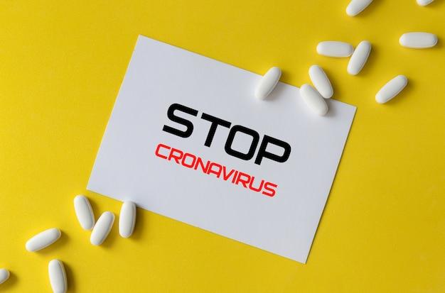 흰색 알 약 및 노란색 배경에 비문 종이. 코로나 바이러스 치료 개념.