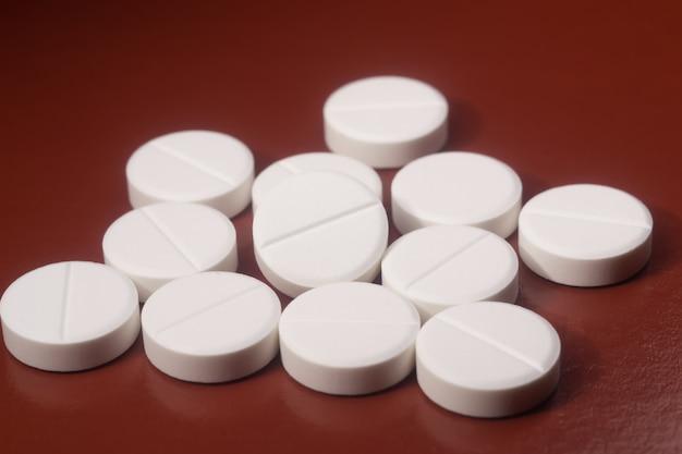 White pills on brown background