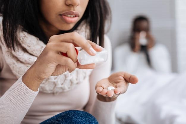 흰색 알약. 그녀의 아픈 피곤 남자 친구를 위해 약을 준비하는 신중한 젊은 집중된 여자